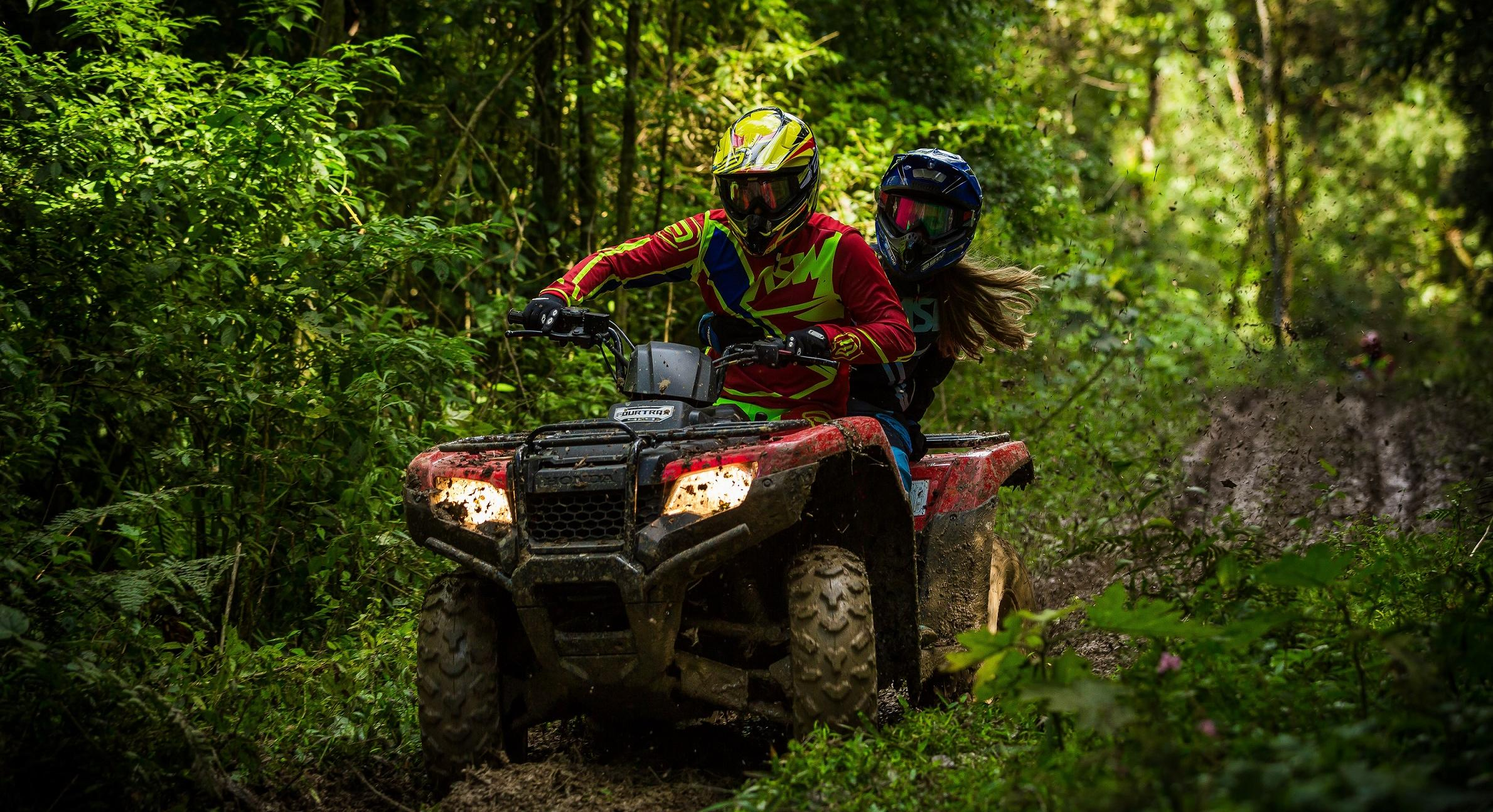 couple riding atv through woods